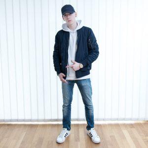 Blaue Bomberjacke von Pull & Bear, weiße Adidas Sneaker, weißer Kapuzenpulli, Esprit Baseballkappe, Jacques Lemans Armbanduhr, Boss Orange Jeans